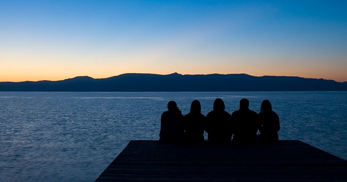 Group of people at end of dock overlooking Lake Tahoe and the sunset over the mountains.