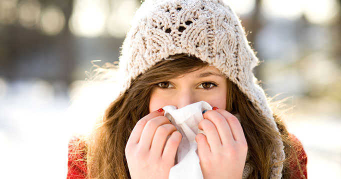 Woman holding tissue to her nose during cold and flu season.