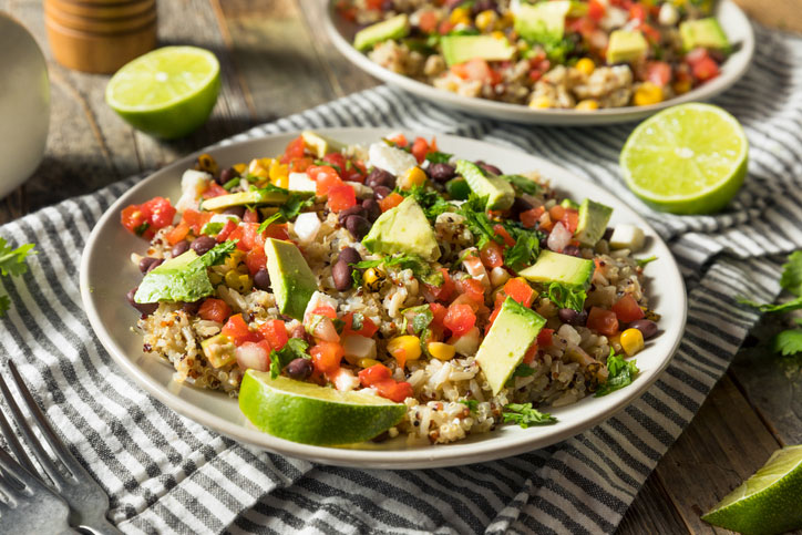 Burrito bowl with lime wedges.