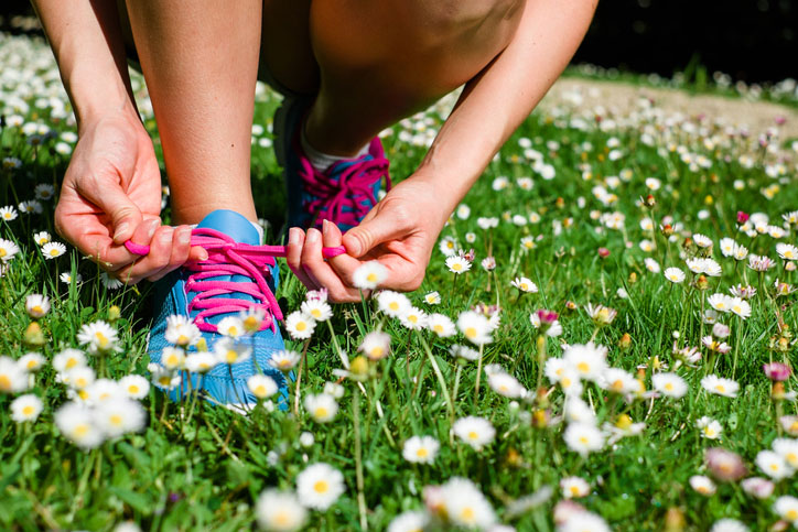 Runner tying shoes in spring grass covered with small flowers.