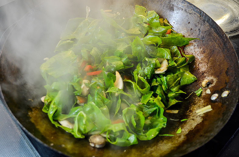Spinach and vegetables cooking in wok.